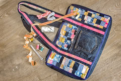 Crafts: bag, made in the style of. Beautiful female bag of colorful scraps of fabric in patchwork. Handmade. Next are the threads, needles, scissors, inch stock image