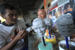Crafts Dolls world and cartoon characters. Craftsmen finish sketching the face of world leaders to serve as miniature dolls in Solo, Central Java, Indonesia stock images
