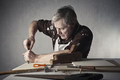 Craftsman. Senior craftsman working some wood boards Royalty Free Stock Photography