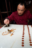 A craftsman. The picture was taken on Oct 23rd 2012 at Jingli Chengdu China. A man with Chinese traditional dress was drawing a bird with melted sugar. It is a Royalty Free Stock Photos