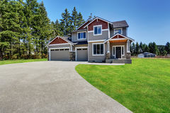 Craftsman American house with rocks trim, garage and concrete floor porch. Classic large craftsman American house exterior with rocks trim, garage and concrete royalty free stock photo