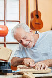 Craftsman as guitar maker works with precision Stock Image
