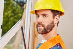 Craftsman as window fitter. Building new house Stock Photos