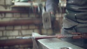 Craftsman blacksmith with hammer in forge creating steel things. Close up stock video