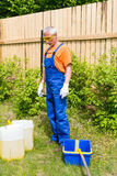 Craftsman in blue and orange uniform looking at paint cans and bucket in the garden. Craftsman in blue and orange uniform and yellow glasses looking at paint royalty free stock photo