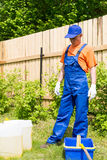 Craftsman in blue overalls and orange T-short looking at paint cans and bucket. In the garden royalty free stock images