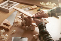 Craftsman building a wooden toy airplane Stock Images