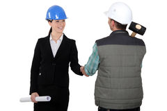 Craftsman and businesswoman shaking hands Royalty Free Stock Image