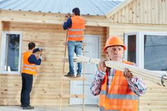 Craftsman carrying wood and working. With carpenters on new house stock photo