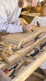 craftsman carving wood in a medieval fair, carpentry tools Stock Image