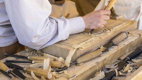 craftsman carving wood in a medieval fair, carpentry tools Stock Photos