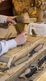craftsman carving wood in a medieval fair, carpentry tools Stock Photo