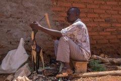 Craftsman carving wood. Craftsman carving a souvenir giraffe of ebony wood in Tanzania Stock Photography