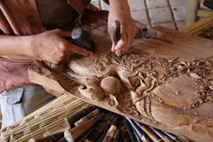 Craftsman carving wood Stock Images