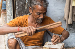 A craftsman carving a wooden printing block for textile block pr Royalty Free Stock Image