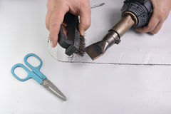Craftsman cleans nozzle with a steel brush Stock Images