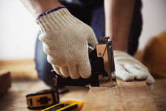 Craftsman with construction tools. Close-up of craftsman hands working with construction instruments on the floor in his workshop Stock Photography