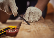 Craftsman with construction tools. Male carver`s hands with chisel working with beam in workshop. Skilled craftsman carving wood Royalty Free Stock Image