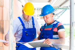 Craftsman controlling building site or construction plans. Construction Team with building plans on site royalty free stock photography