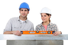 Craftsman and craftswoman building wall Royalty Free Stock Photo