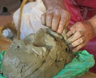 Craftsman creates a clay mask using skilled hands Royalty Free Stock Photo