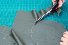 Craftsman cuts the bottom of pouch from leather royalty free stock image