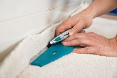 Craftsman cutting carpet Royalty Free Stock Image