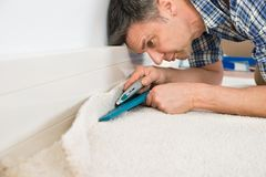 Craftsman cutting carpet Stock Images