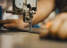 Craftsman cutting an iron rod using a hacksaw. Craftsman cutting an iron rod with a hacksaw Royalty Free Stock Photo