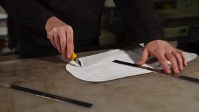 Craftsman cutting paper template. Craftsman making template for handiwork. He cutting cliche from the paper with utility knife stock footage