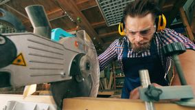 Craftsman is cutting wood with a circular saw. 4K stock footage
