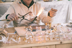 Craftsman decorating glass objects with a torch. Stock Photos