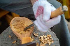 Craftsman demonstrates the process of making wooden spoons handmade using tools. National crafts concept. Craftsman demonstrates the process of making wooden stock photo