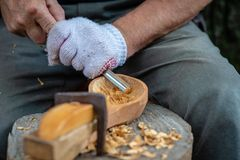 Craftsman demonstrates the process of making wooden spoons handmade using tools. National crafts concept. Craftsman demonstrates the process of making wooden royalty free stock photos