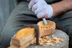 Craftsman demonstrates the process of making wooden spoons handmade using tools. National crafts concept. Craftsman demonstrates the process of making wooden royalty free stock image