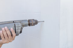Craftsman drilling holes into the white wall Stock Images