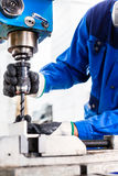 Craftsman drilling metal with drill Stock Photos