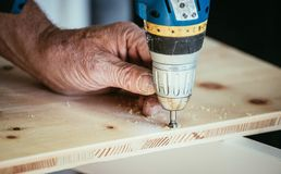 Craftsman is drilling in wood with drilling machine. Tools workman handcrafter power screw trade woodwork furniture skill talent carpenter joiner amateur stock image