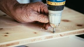 Craftsman is drilling in wood with drilling machine. Tools workman handcrafter power screw trade woodwork furniture skill talent carpenter joiner amateur royalty free stock photos