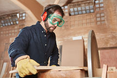 Craftsman with ear protection. Craftsman working with ear protection and googles Stock Image