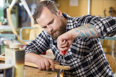 Craftsman files wooden guitar neck in workshop. Carpenter using file on a guitar neck in a workshop for wood. Man with tattoo and beard working with musical royalty free stock photography