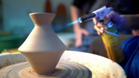 Craftsman finishes the creation of clay jug in his workshop. Man burns product using gas jet flame burner gun. Crafting. Artwork, handmade concept. Slow motion stock video