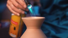 Craftsman finishes the creation of clay jug in his workshop. Man burns product using gas jet flame burner gun. Crafting. Artwork, handmade concept. 4k stock video