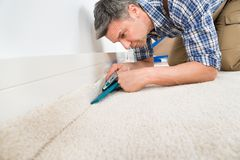 Craftsman fitting carpet Stock Photography