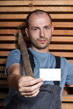 Craftsman with a hammer holding a business card. Craftsman with a big hammer holding a business card on wooden background Royalty Free Stock Photos