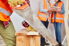 Craftsman with hand saw cutting wood. At construction site Royalty Free Stock Photos