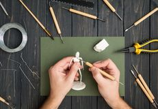 Craftsman hands working on human sculpture, sculpturing from polymer clay against working table with tools. Flat lay, top view. Craftsman hands working on human Stock Image
