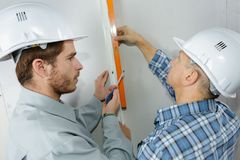 Craftsman with hardhats level controlling stock images