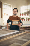 Craftsman in his studio holding up a framed bank note Stock Photo