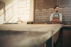 Craftsman in his workshop looking away with arms crossed confide Stock Image